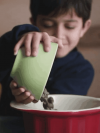 boy pouring chocolate chips into a bowl